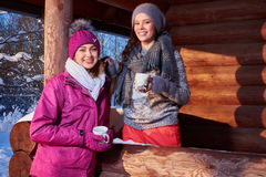 Happy girlfriends spend winter holidays at mountain cottage Royalty Free Stock Photo
