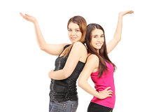 Happy girlfriends standing close together and gesturing with the Stock Photo