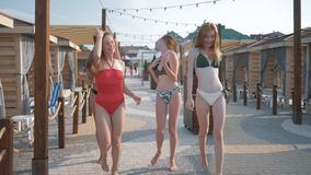 Happy girlfriends, young women with beautiful slender bodies in swimsuits running, having fun and laughing during sea