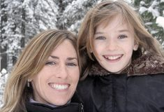 Happy Girls. Smiling mother and daughter with snow covered pine trees in background Stock Photography