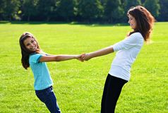 Happy girls. Older and younger sisters stand in the field on a sunny day smiling and holding hands Royalty Free Stock Photo