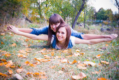 Happy girls in autumn leaves. Two happy girls lying in autumn leaves Stock Photography