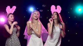 Happy girls at bachelorette party blowing soap bubbles. Slow motion. Happy girls having fun at bachelorette party and blowing soap bubbles, against disco lights stock footage