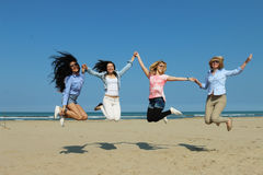 Happy girls on beach jumping together. Best friends, 4  happy joyful girl friends from multi racial backgrounds jump on beach with joy and happiness Stock Photo