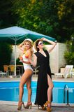 Happy girls with beverages on summer party near the pool. royalty free stock image