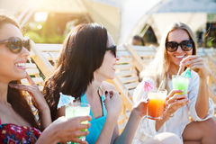 Happy girls with beverages on summer party. Near the pool Stock Photo