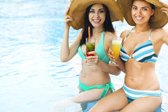 Happy girls with beverages on summer party. Near the pool stock photos