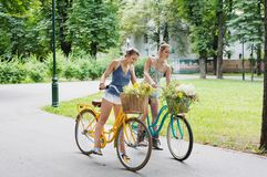 Happy boho chic girls ride together on bicycles in park royalty free stock photo