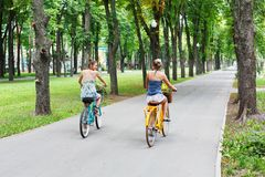 Happy boho chic girls ride together on bicycles in park royalty free stock photos
