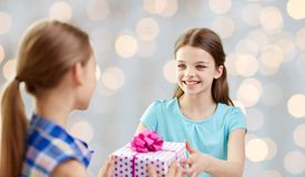 Happy girls with birthday present over lights Royalty Free Stock Photography