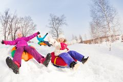 Happy girls and boy slide on colorful tubes. With arms up during beautiful winter day with trees trunks on the background Stock Image
