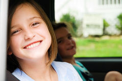 Happy Girls in a Car. Two smiling, happy, girls sitting in a car, with seat belts on