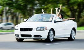 Happy girls in the car with arms outstretched Royalty Free Stock Photo
