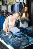 Happy girls choosing denim trousers Stock Photography