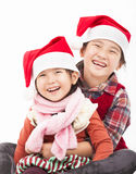 Happy girls in christmas hat. Happy asian girls in christmas hat and sitting together Stock Images