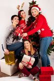 Happy Girls with Christmas tree and gift boxes. Happy Four Girls in wool sweater with gift boxes and Christmas tree and decoration. Xmas and New Year holiday Stock Images