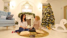 Happy girls communicate and have fun, sit on floor on background of fireplace and Christmas tree in large living room stock video