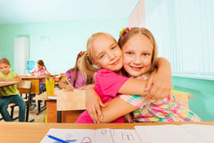 Happy girls in a cuddle sitting together at desk Royalty Free Stock Photo