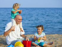 Happy  girls with dad  on  sea shore Royalty Free Stock Images