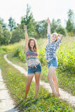 Happy girls dancing near farm field Stock Images