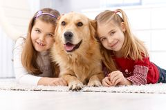 Happy girls with dog smiling at home. Happy little girls lying prone on floor at home with golden retriever, smiling stock photos