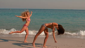 Happy girls doing a cartwheel on the beach. In slow motion stock video
