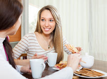 Happy girls  drinking tea and gossiping. In home Royalty Free Stock Photo
