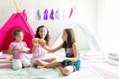 Girls Enjoying Fresh Donuts While Sitting Against Teepee Tents. Happy girls enjoying fresh donuts while sitting against teepee tents at home stock photos