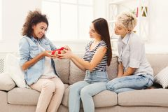 Excited woman getting gift from her friends. Happy girls exchanging gifts. Excited women getting present from her friends. Birthday, holidays, celebration and Royalty Free Stock Photos