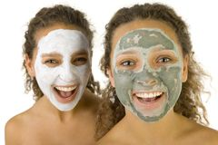 Happy girls with face masks. Happy young women with masks anti-aging. Focus on first person. They're on white background Royalty Free Stock Images