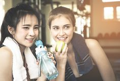 Happy girls friends is eating fruit and water in fitness. Happy girls friends is eating fruit and fresh water in fitness royalty free stock image