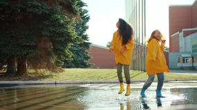 Happy girls friends jumping dancing in puddle wearing raincoats and rainboots. Happy girls friends are jumping dancing in puddle wearing raincoats and rainboots stock video footage