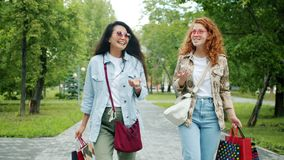 Happy girls friends walking in park holding shopping bags laughing talking. Happy girls friends are walking in park holding shopping bags laughing talking stock video