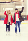 Happy girls friends waving hands on skating rink Royalty Free Stock Photos