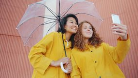 Happy girls friends wearing raincoats holding umbrella taking selfie outdoors. Using smartphone camera posing having fun. Autumn weather and photo concept stock video footage
