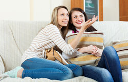 Happy girls  gossiping on sofa Royalty Free Stock Photography