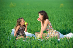 Happy girls on green grass with fruits Stock Photo
