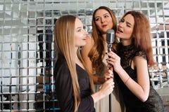 Happy girls having fun singing at a party. stock image