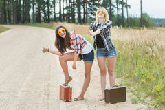 Happy girls hitchhike with cardboard on road Stock Photos