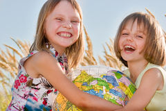 Happy girls holding globe Stock Image