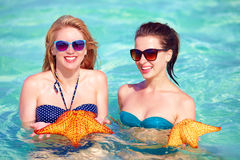 Happy girls holding star fish, summer vacation Stock Photo