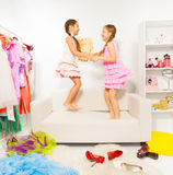 Happy girls jump and hold hands on white sofa Stock Images