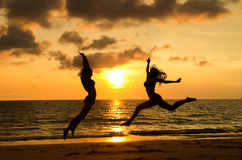 Happy girls jumping on the beach. During sunset, summer vacation in Thailand Stock Photo