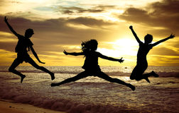 Happy girls jumping on the beach at the sunset time. Stock Photo
