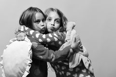 Happy girls. Kids with funny faces make air kisses and hold pillows. Happy girls. Kids with funny faces make air kisses and hold green and yellow sun pillows stock image