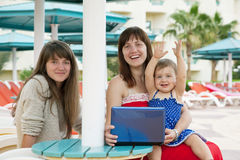 Happy girls with laptop at resort Stock Photography