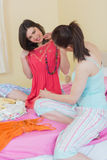 Happy girls looking at a dress at a sleepover Royalty Free Stock Photo