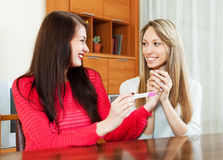 Happy girls looking at pregnancy test. At home interior royalty free stock images