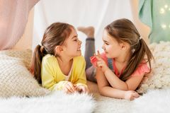 Happy girls lying in kids tent and talking at home. Childhood, hygge and friendship concept - happy girls lying in kids tent and talking at home royalty free stock photos