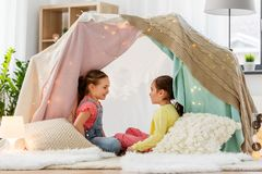 Happy girls lying in kids tent and talking at home. Childhood, hygge and friendship concept - happy girls lying in kids tent and talking at home stock photo